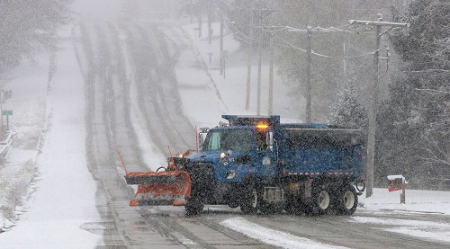 A City of Sheboygan snow plow truck drives down a snowy street.
